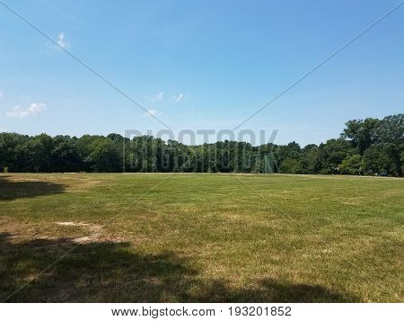 large grass field with baseball diamond and fence and blue sky