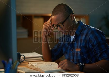 Profile view of concentrated young student preparing for exam while sitting at table in dim bedroom, blurred background