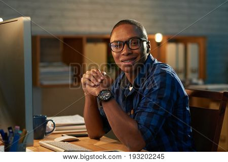Smiling African American entrepreneur looking at camera while sitting in front of computer in dim office, wast-up portrait