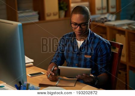 Waist-up portrait of young handsome student taking notes while preparing for exam with help of digital tablet, interior of dark room on background
