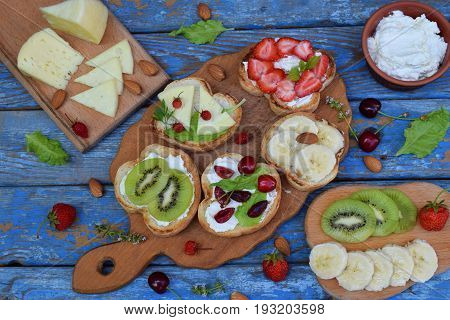 Set Of Assorted Healthy Wholewheat Bread Sandwiches With Fruit, Cheese And Leafy Green Herbs On Picn