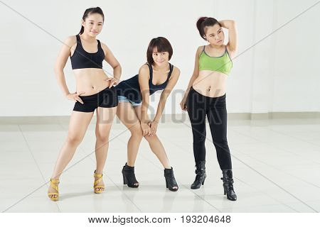 Attractive Asian dancers gathered together in spacious dance hall and posing for photography, full length group portrait