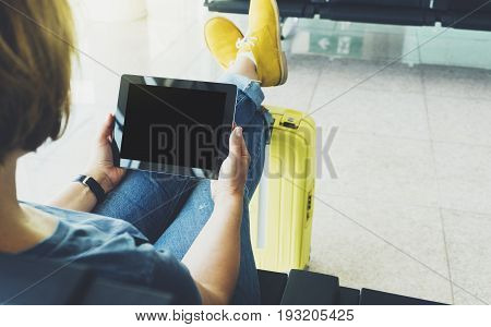 Young hipster girl sitting at airport and put feet in yellow boot on suitcase traveling in Europe female hands texting message on gadget in terminal area hall summer journey trip concept mockup blank screen tablet