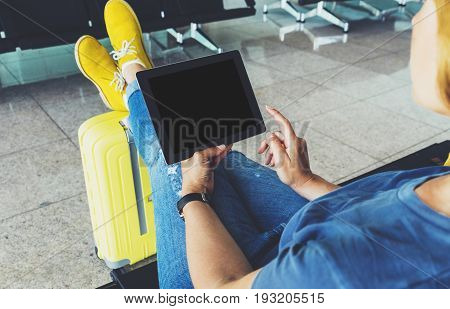 Young hipster girl at airport and put feet in yellow boot on suitcase waiting air flight female hands holding computer in terminal departure lounge gate traveler trip concept mock up of blank screen tablet