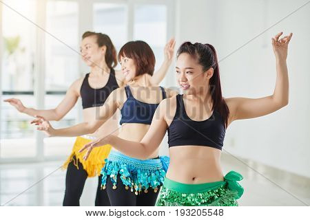 Pretty Asian women wearing colorful hip scarfs standing in row and practicing in belly dance, interior of dance hall on background