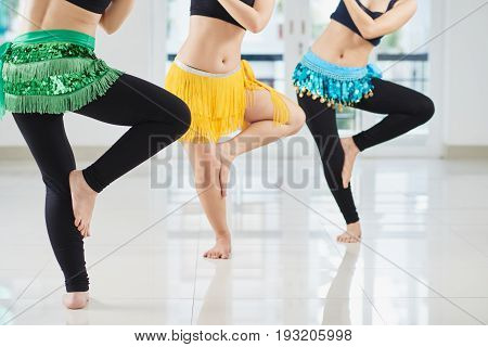 Unrecognizable belly dancers wearing hip scarfs enjoying each others company while dancing together in spacious hall