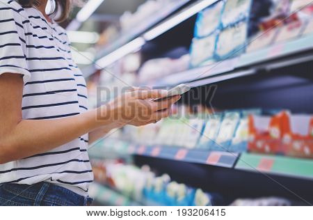 Woman shopping healthy food in supermarket background. Close up view girl buy products using digital gadget in store. Hipster at grocery using smartphone. Person comparing the price of produce