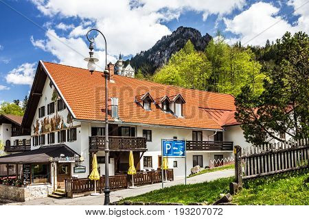 Bavaria, Germany - May 30, 2017: Painted rural house and Neuschwanstein castle
