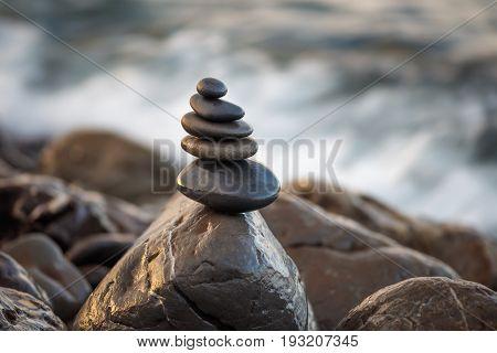 Stones pyramid on pebble beach symbolizing stability harmony balance. Shallow depth of field.
