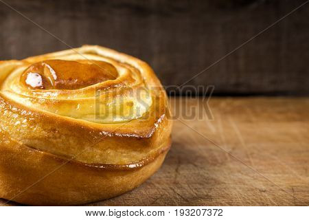 Fresh sweet homemade cinnamon roll. Svedish cuisine. Dark wood background with copy space