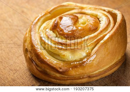 Close up of fresh sweet homemade cinnamon roll. Svedish cuisine. Dark wood background
