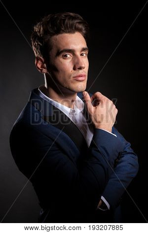 Succesful man in suit on black background in studio photo. Succesful fashionable businessman