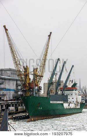 Dry cargo vessel in sea port Odessa in winter, Ukraine.