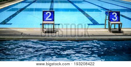 Jumping stands marked number two and three in the lanes of swimming pool water sport swimming pool center.
