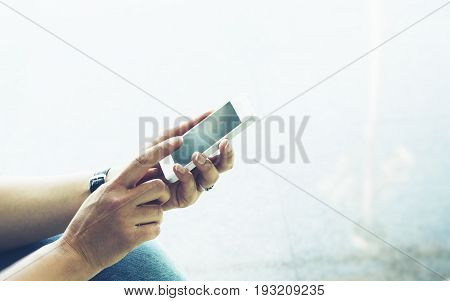 Young hipster girl sitting at airport and traveling in Europe female hands using app on making smartphone gadget in terminal area hall tourist traveler trip concept mockup blank screen sell phone