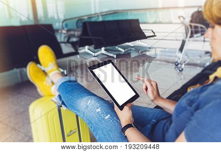 Young hipster girl at airport in yellow boot on suitcase waiting air flight female hands holding computer in terminal departure lounge gate traveler trip concept mock up of blank screen tablet