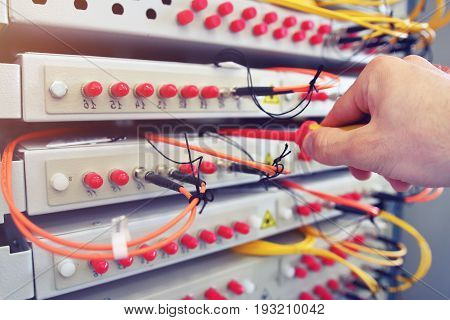 Engineer is setting up industrial optical telecommunications switchboard in date center. Fiber optical switch with connected FC cables in server room