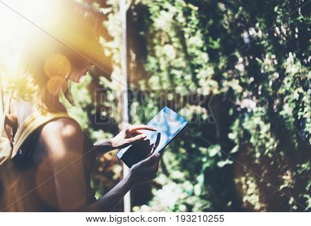 Hipster young girl with bright backpack and vintage camera using tablet or holding gadget planning travel plan. View tourist traveler on background Parc Laberint Barcelona. Mock up for text message
