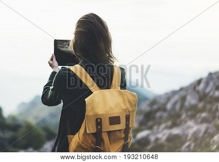 Hipster young girl with bright backpack enjoying sunset on peak of foggy mountain. Tourist traveler on background valley landscape view mockup. Hiker photographing on device in trip in northern spain basque country mock up for text. Picos de Europa