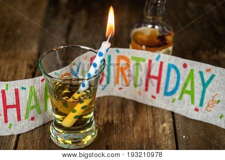 candle and whiskey in shot glass with birthday banner and bottle on rustic wood