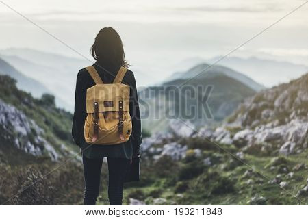 Hipster young girl with bright backpack enjoying sunset on peak of foggy mountain. Tourist traveler on background valley landscape panoramic view mockup. Hiker looking sunlight in trip in northern spain basque country mock up for text. Girl taking photo o