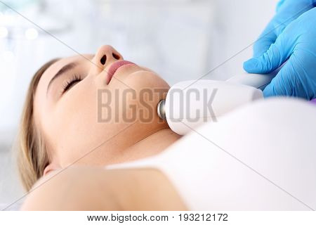 Firming the skin of the neck. The vacuum neck massage using a special head. Woman in the clinic of aesthetic medicine.