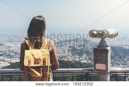 Hipster young girl with bright backpack looking on observation deck and planning travel plan. View from the back of the tourist traveler on background panoramic view of the city coin operated binoculars. Mock up for text message. Barcelona Tibidabo