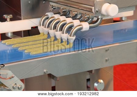 A Food Processing Machine Extruding Strips of Food.