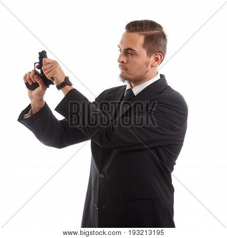A man in a suit reloading a handgun