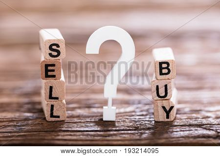 Close-up Of Buy Or Sell Option On Wooden Block With White Question Mark Sign
