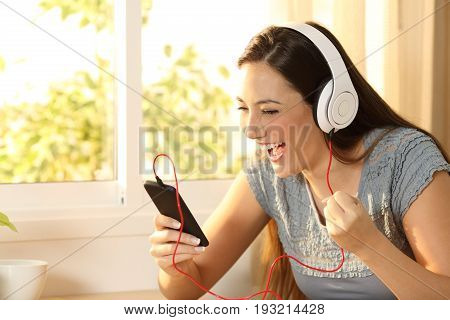 Excited woman watching content and listening music with headphones and smart phone