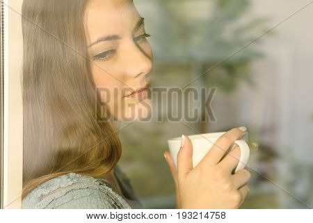 Pensive lady looking through a window holding a cup of coffee