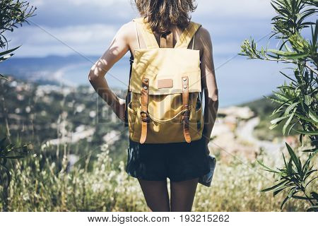 Hipster young girl with bright backpack looking at a map and poining hand the travel plan. View from the back of the tourist traveler on background mountain sea. Mock up for text message