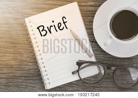 Concept Brief on notebook with glasses pencil and coffee cup on wooden table.