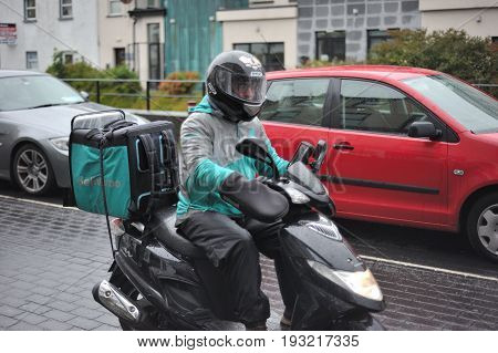 Galway, Ireland June 2017,deliveroo Guy Making A Delivery In A Scooter.