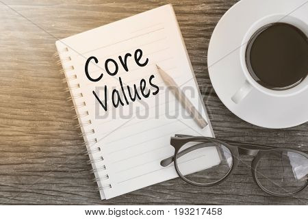 Concept Core values on notebook with glasses pencil and coffee cup on wooden table.