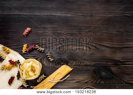 Assortment of different shape italian pastas on grey wooden table top view copyspase.