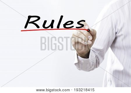 Businessman hand writing Rules with red marker on transparent wipe board business concept