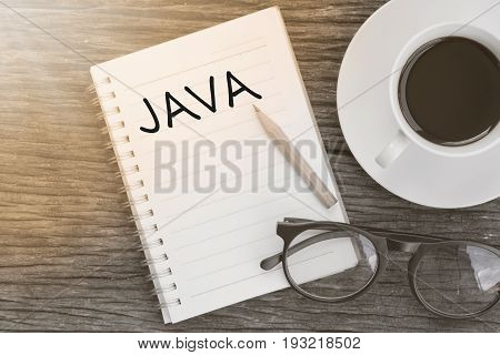 Concept JAVA on notebook with glasses pencil and coffee cup on wooden table.