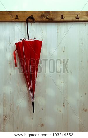 Wet umbrella hanging up to dry on hook