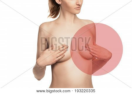 nude Female breast. Young caucasian adult woman examining her breast for lumps or signs of breast cancer with red sign of disease.