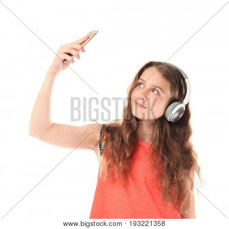 Cute teenager girl with headphones taking selfie on white background