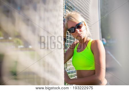 young adult sporty girl stands near the football nets