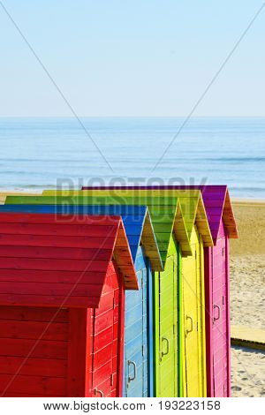 closeup of some colorful beach huts of different colors in a lonely beach, with the ocean in the background and a blank space on top