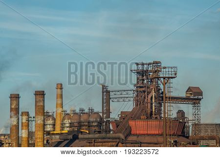 Pipes of heavy metallurgical industry pollute the air on background of the blue sky. Pollution of the environment. Fuming rusty Lipetsk Metallurgical Plant