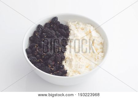 Morus nigra called Mulberry with black color and cottage cheese . In white plate. Mulberries Food Background.