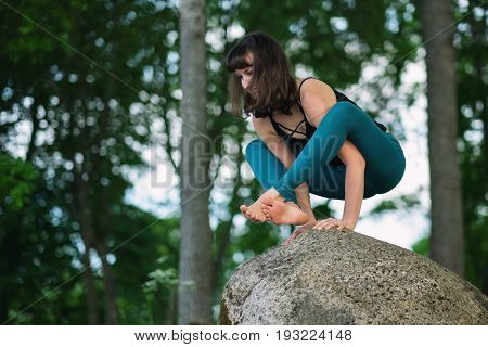 Side view of caucasian practicing yoga, standing in hand balance exercise, Bakasana pose, working out on big stone in nature