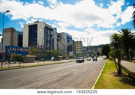 QUITO, ECUADOR - MAY 06 2016: Unidentified people waling in the mainstreet in NNUU avenue with some buildings, cars and people in the city of Quito.