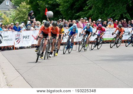 STILLWATER, MINNESOTA - JUNE 18, 2017: Group of pro cyclists in peloton chase  leaders at the 2017 North Star Grand Prix Women's Stillwater Criterium. It is the final stage of a six-stage annual race.