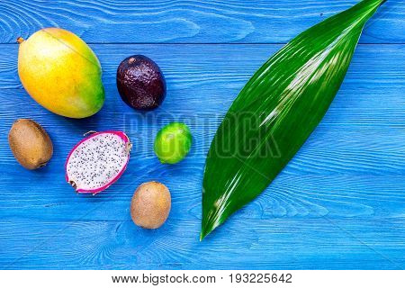 Exotic fruits dragonfruit, mangosteen, mango, kiwi and lime on blue wooden background top view.